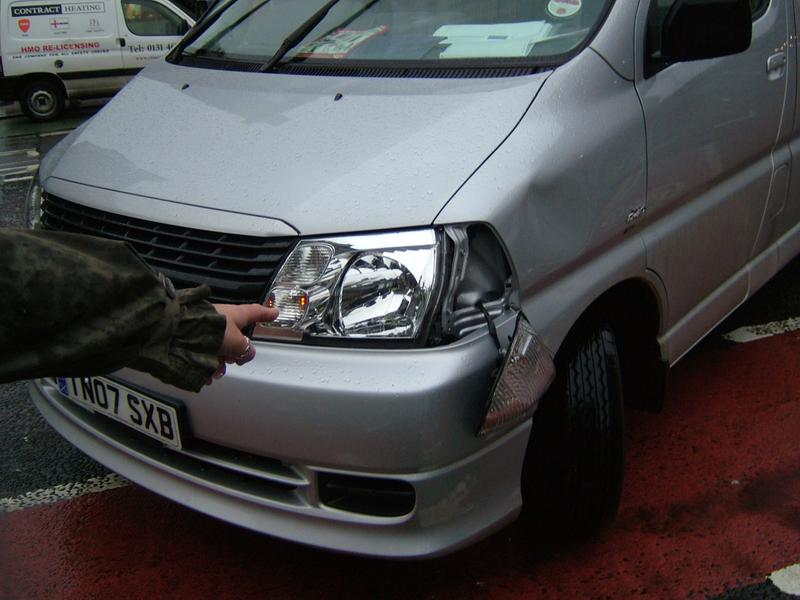 Front of van showing damaged light and dent to body work
