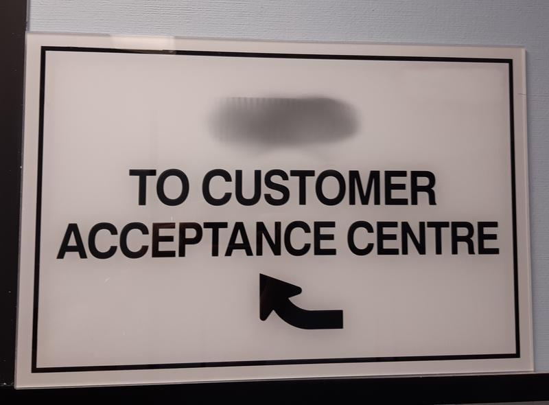 Sign directing 'To Customer Acceptance Centre'
