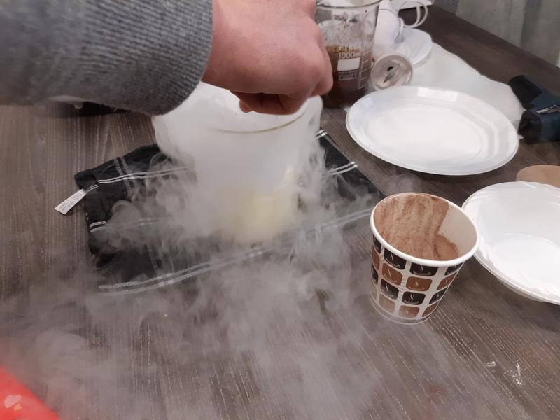 Glass beaker being stirred while white vapour flows out of it.